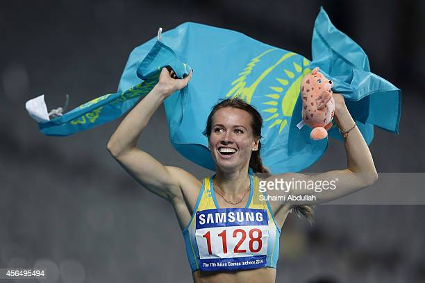 Olga Safranova celebrates a victory lap after winning the gold medal in the Women's 200m Final on day twelve of the 2014 Asian Games at Incheon Asiad...