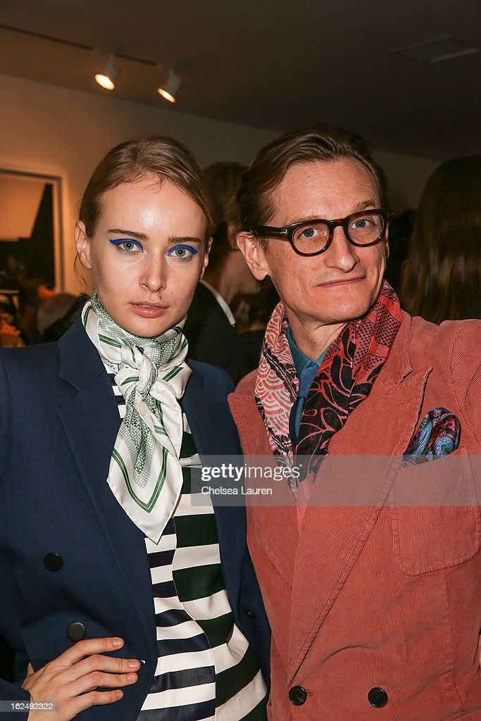Olga Sorokina (L) and international editor at large of Vogue Hamish Bowles visit the Mario Testino opening at PRISM during Academy Awards week on February 23, 2013 in Los Angeles, California.