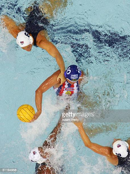 Olga Turova of Russia tries to retain control of the ball as she is surrounded by a group of USA defenders in the women's Water Polo preliminary game...
