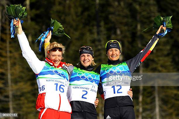 Olga Zaitseva of Russia celebrates winning silver, Magdalena Neuner of Germany gold and Simone Hauswald of Germany bronze during the flower ceremony...