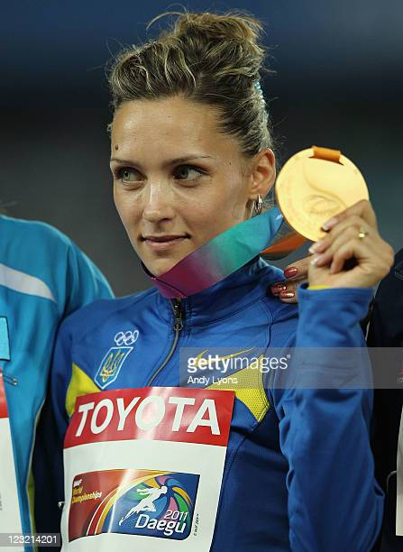 Olha Saladuha of Ukraine poses with the gold medal following her victory in the women's triple jump final during day six of the 13th IAAF World...