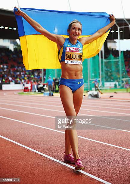 Olha Saladukha of Ukraine poses with the Ukrainian national flag as she celebrate winning gold in the Women's Triple Jump final during day five of...