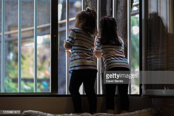 Olimpia and Maya, the photographer's 3-year-old daughters, look out of the window a day before they are allowed to go outside on April 25, 2020 in...