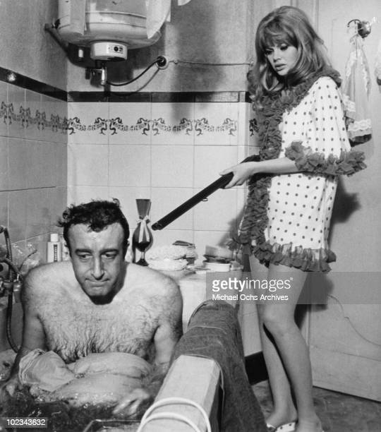 Olimpia Segura points a shotgun at Juan Bautista forcing him to dye himself blue in a bathtub in a scene from the movie The Bobo which was released...