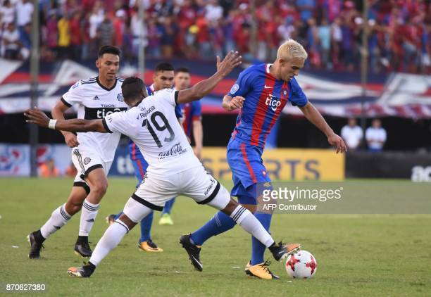 Olimpia's Farid Diaz vies for the ball with Cerro Porteno's Alfio Oviedo during the Paraguayan derby match in the 2017 Clausura tournament at the...