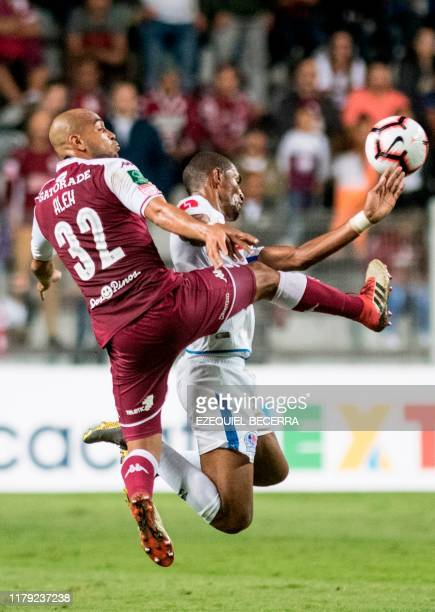 Olimpia's Jerry Bengtson vies for the ball with Saprissa's Alexander Robinson during the Concacaf Champions League semifinal football match between...