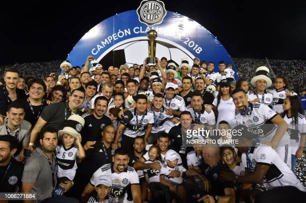 Olimpia's players celebrate with the trophy after winning the Paraguayan Clausura 2018 tournament at the Defensores del Chaco stadium in Asuncion on...