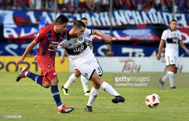 Olimpia's Uruguayan Alejandro Silva passes the ball challenged by Cerro Porteno's Marcos Caceres during the Paraguayan Apertura football tournament...