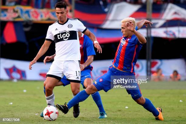 Olimpia's Walter Gonzalez vies for the ball with Alfio Oviedo during the Paraguayan derby match in the 2017 Clausura tournament at the Defensores del...