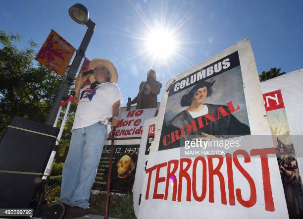 Olin Tezcatlipoca from the Mexica Movement speaks to demonstrators in front of a statue of Christopher Columbus during a protest against Columbus Day...