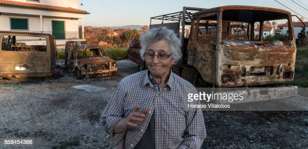 Olinda Conceicao Martins reacts while standing before three of the family five burned vehicles four months after the forest fire on October 06 2017...
