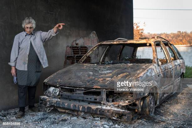 Olinda Conceicao Martins reacts while standing by one of the family five burned vehicles four months after the forest fire on October 06 2017 in Vila...