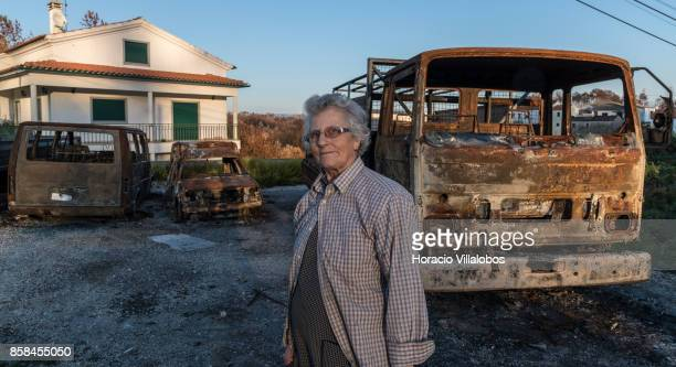 Olinda Conceicao Martins stands before three of the family five burned vehicles four months after the forest fire on October 06 2017 in Vila Facaia...