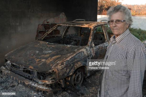 Olinda Conceicao Martins stands by one of the family five burned vehicles four months after the forest fire on October 06 2017 in Vila Facaia...