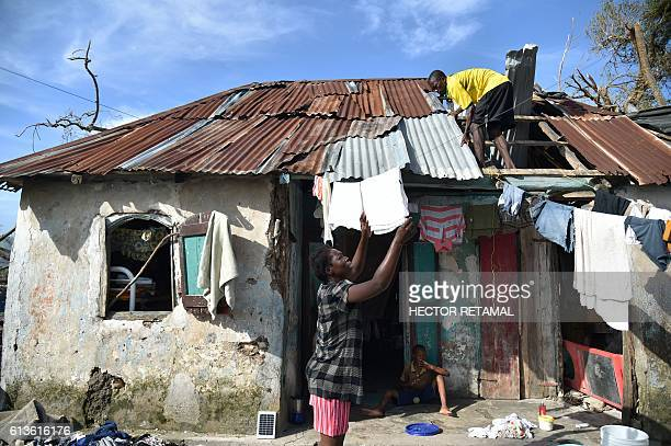 Olivar repairs the roof of his home damaged by Hurricane Matthew in a rural zone of Les Cayes in the Southwest of Haiti on October 9 2016 Haiti began...