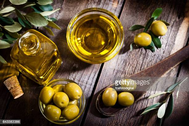 olive oil and green olives shot from above - green olive stock photos and pictures