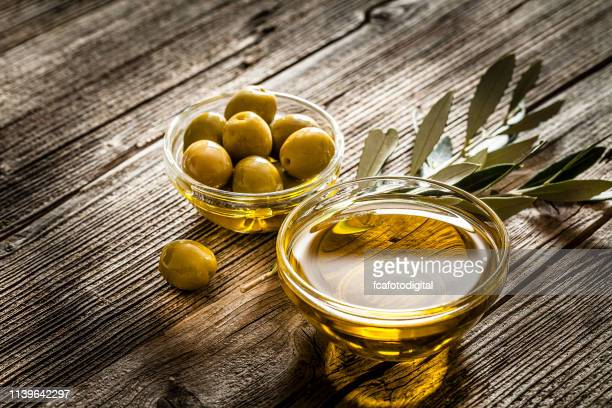 olive oil and green olives shot on rustic wooden table - extra virgin olive oil stock pictures, royalty-free photos & images