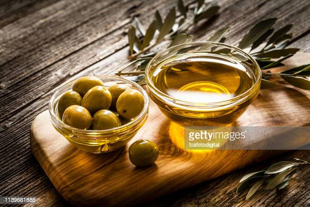 olive oil and green olives shot on rustic wooden table - green olive fruit stock pictures, royalty-free photos & images