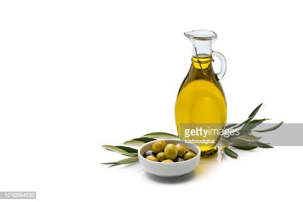 olive oil and olives isolated on reflective white background - olive oil stock pictures, royalty-free photos & images