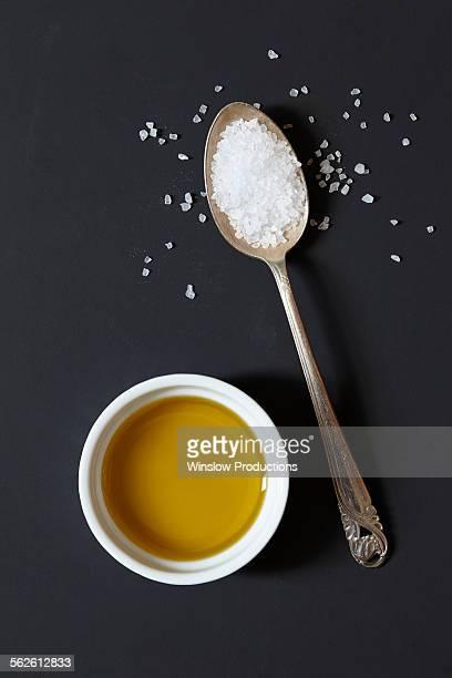 Olive oil and salt on black background
