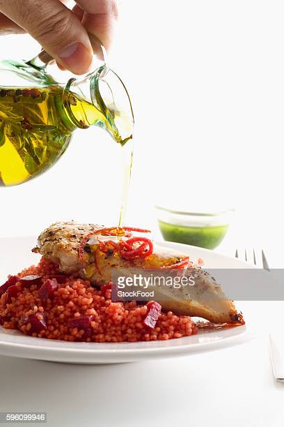 Olive oil being drizzled over a chicken breast on a bed of beetroot couscous