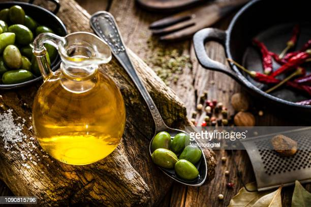olive oil bottle and green olives shot on rustic wooden table - olive oil stock pictures, royalty-free photos & images