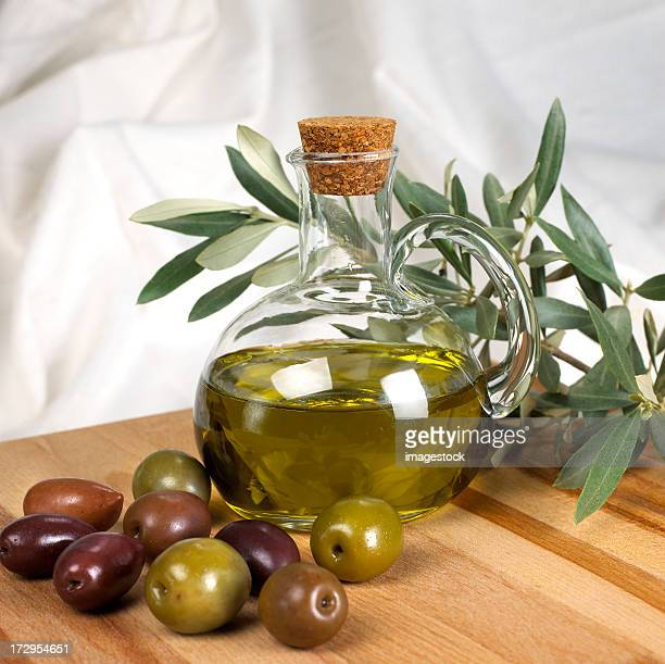 Olive oil bottle and olives on a wooden surface