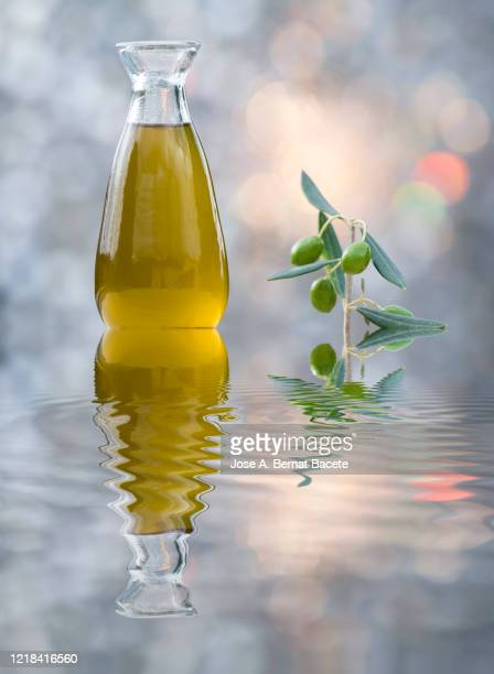 olive oil bottle on a water surface illuminated by sunlight. - extra virgin olive oil stock pictures, royalty-free photos & images
