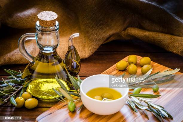 olive oil bottle with olive branch on a olive wooden cutting board with copy space - olive oil stock pictures, royalty-free photos & images