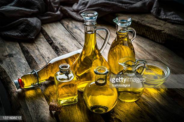olive oil bottles collection on rustic wooden table - extra virgin olive oil stock pictures, royalty-free photos & images
