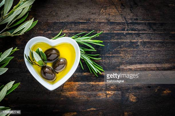 olive oil in a heart shaped bowl. copy space. - extra virgin olive oil stock pictures, royalty-free photos & images