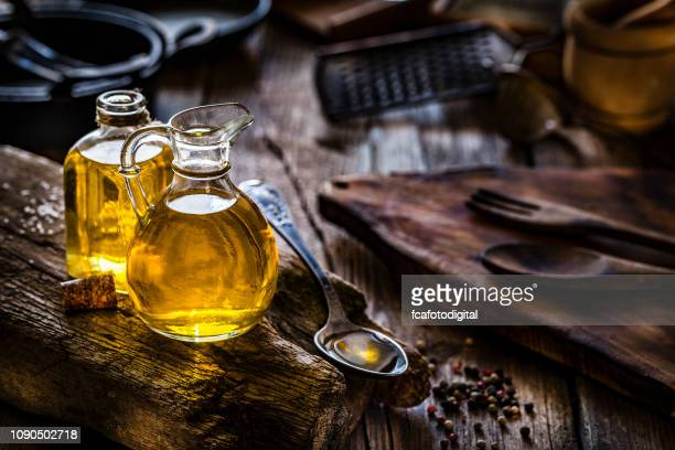 olive oil in glass bottles shot on rustic wooden table - extra virgin olive oil stock pictures, royalty-free photos & images