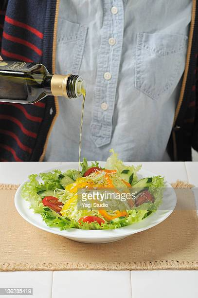Olive oil is poured on the vegetable salad.