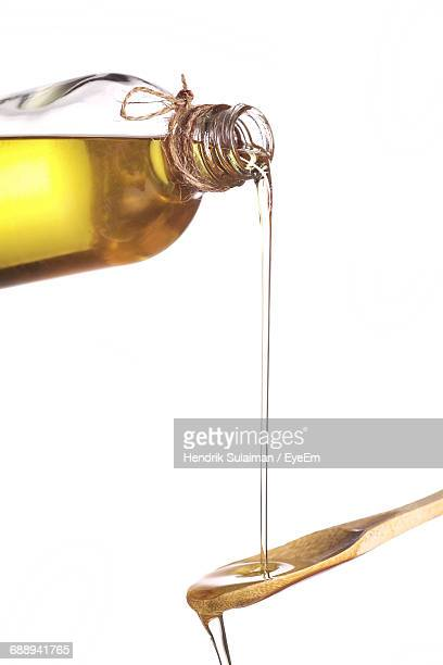 Olive Oil Pouring From Bottle On Wooden Spoon Against White Background
