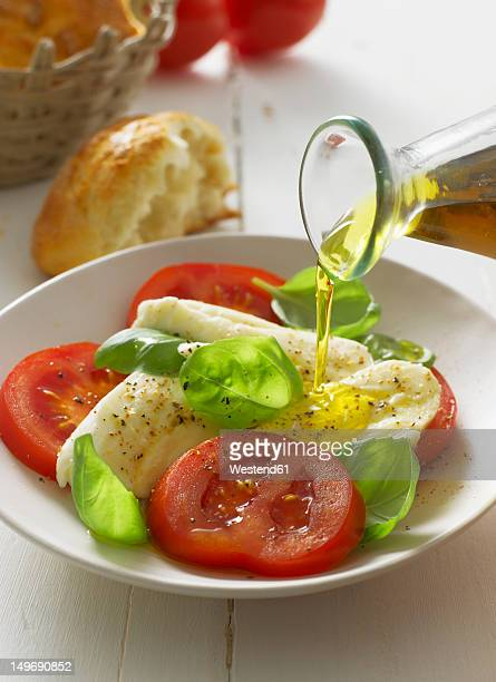 Olive oil pouring on caprese salad in plate, close up