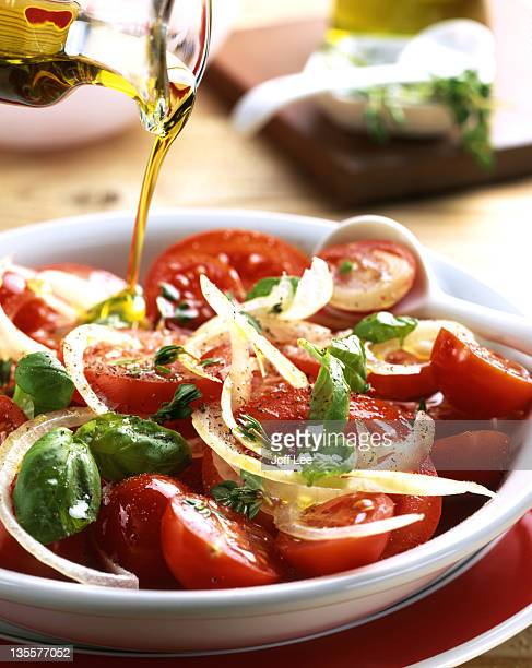 olive oil pouring over tomato and basil salad - olive oil stock pictures, royalty-free photos & images