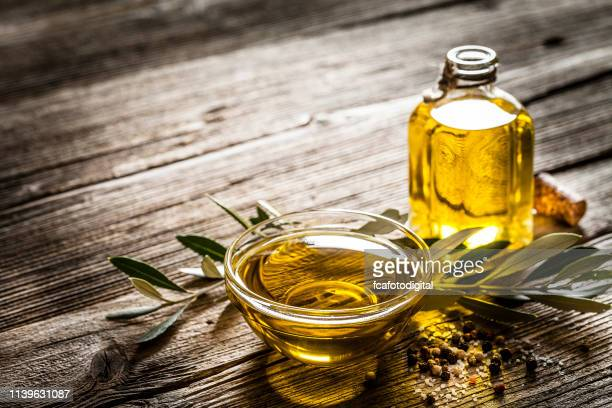 olive oil shot on rustic wooden table with copy space - extra virgin olive oil stock pictures, royalty-free photos & images