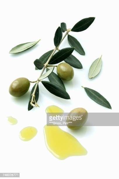 a olive sprig with olives next to a pool of olive oil - aceitunas fotografías e imágenes de stock