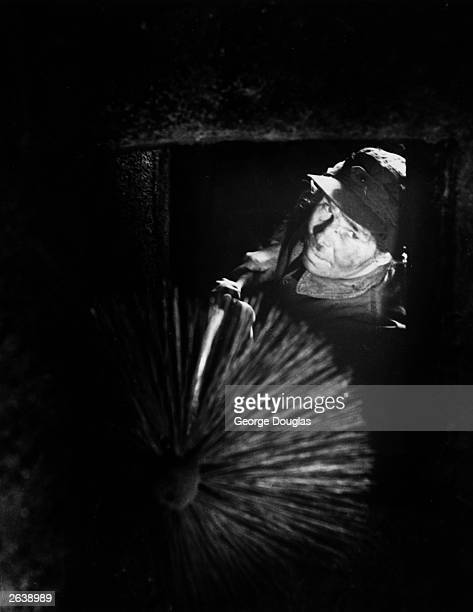 Olive Walker one of the few female chimney sweeps in the country cleaning a chimney in the village of Worplesdon near Guildford in Surrey Original...