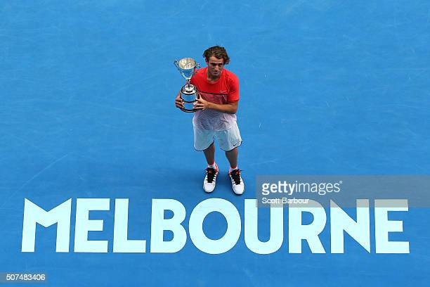 Oliver Anderson of Australia poses with the championship trophy after winning his Junior Boys' Singles Final match against Jurabeck Karimov of...