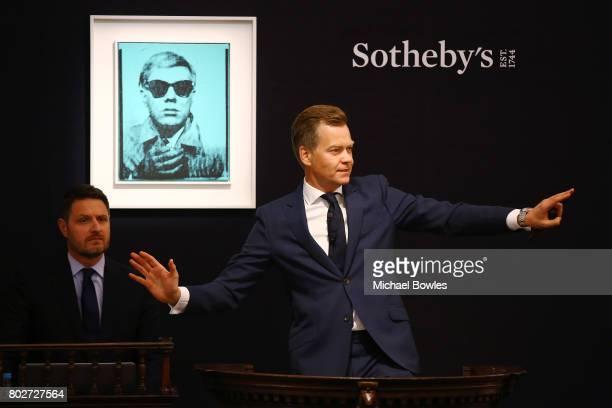 Oliver Barker, SothebyÕs European Chairman, fields bids for Andy WarholÕs ÔSelf PortraitÕ from 1963-64, during the Contemporary Art Evening Auction...