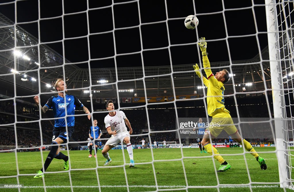 Oliver Baumann of 1899 Hoffenheim saves a shot at goal from Robert Lewandowski of Bayern Munich during the Bundesliga match between TSG 1899 Hoffenheim and Bayern Muenchen at Wirsol Rhein-Neckar-Arena on April 4, 2017 in Sinsheim, Germany.