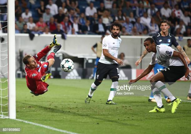 Oliver Baumann of Hoffenheim saves against Joel Matip of Liverpool while Mohamed Salah looks on during the UEFA Champions League Qualifying PlayOffs...