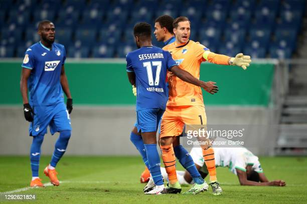 Oliver Baumann of TSG 1899 Hoffenheim celebrates with teammate Ryan Sessegnon after saving a penalty during the DFB Cup second round match between...