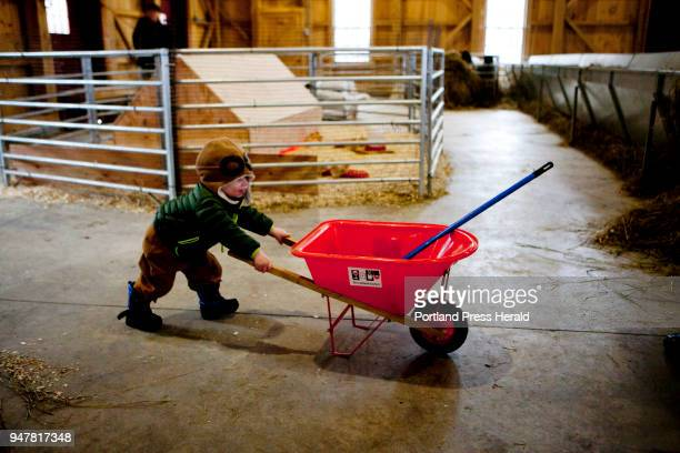 Oliver Belanger of Old Orchard Beach pushes a wheelbarrow around the barn during the First Time Farmers program at Wolfe's Neck Center in Freeport on...