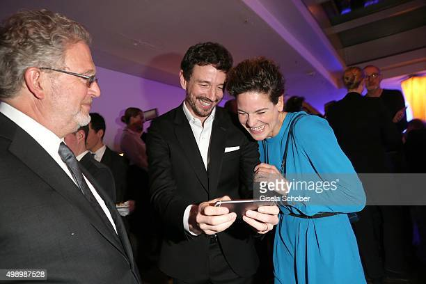 Oliver Berben shows his baby son on the smart phone to Bibiana Beglau during the ARD advent dinner hosted by the program director of the tv station...