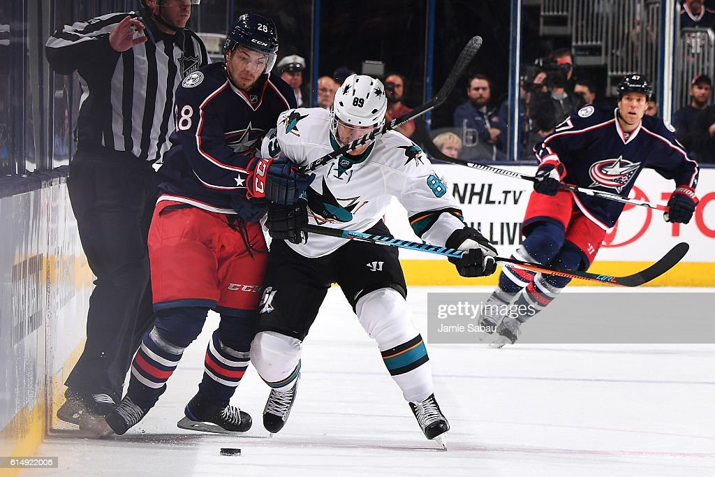 Oliver Bjorkstrand #28 of the Columbus Blue Jackets and Mikkel Boedker #89 of the San Jose Sharks battle for a loose puck during the third period of a game on October 15, 2016 at Nationwide Arena in Columbus, Ohio. San Jose defeated Columbus 3-2.