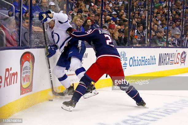 Oliver Bjorkstrand of the Columbus Blue Jackets checks Erik Cernak of the Tampa Bay Lightning into the boards while chasing after the puck during the...