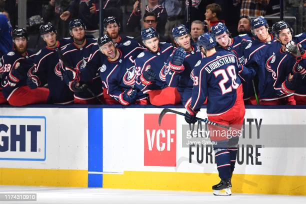 Oliver Bjorkstrand of the Columbus Blue Jackets highfives his teammates after scoring a goal during the first period in a game against the Buffalo...