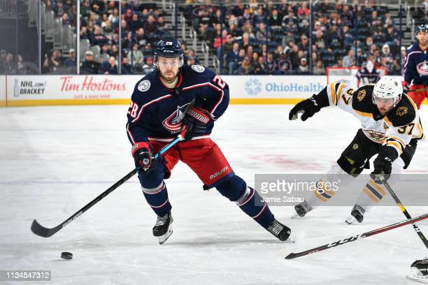 Oliver Bjorkstrand of the Columbus Blue Jackets skates with the puck as Patrice Bergeron of the Boston Bruins attempts to block a passing lane during...